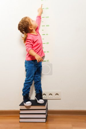 Girl checking height on growth chart