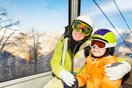 Mom and son skiers sit in cable car ski lift