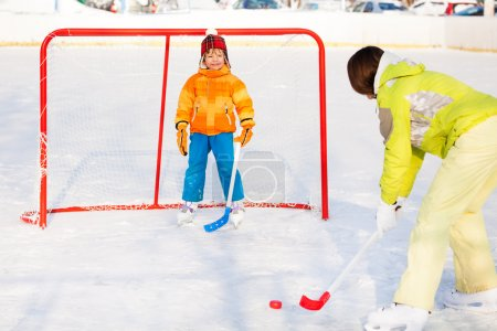 Mother play ice hockey with son outside