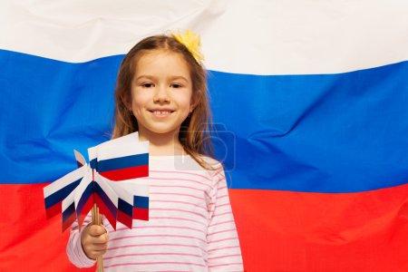 Photo pour Fillette souriante tenant beaucoup de drapeaux dans ses bras contre le drapeau de la Fédération de Russie - image libre de droit