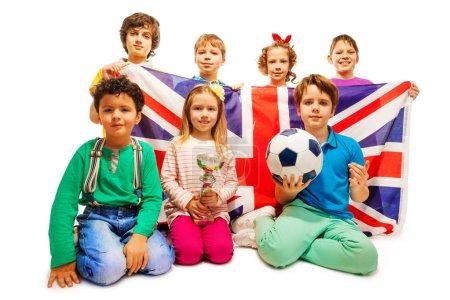 Photo pour L'équipe des sept gagnants de football anglais avec coupe, boule et drapeau de la Grande-Bretagne, isolée sur fond blanc - image libre de droit