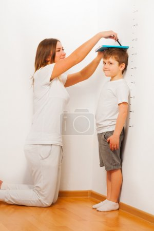 Mother measuring her son's height