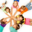 Large group of kids laying on a white floor with h...