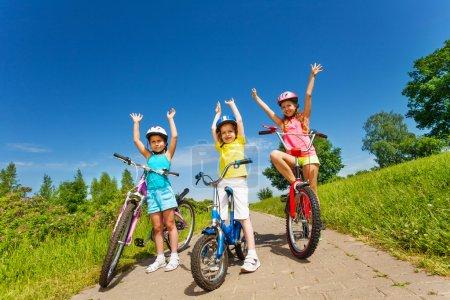 Photo pour Trois petites filles à vélo lèvent la main sur une route pavée par une journée ensoleillée dans le parc - image libre de droit