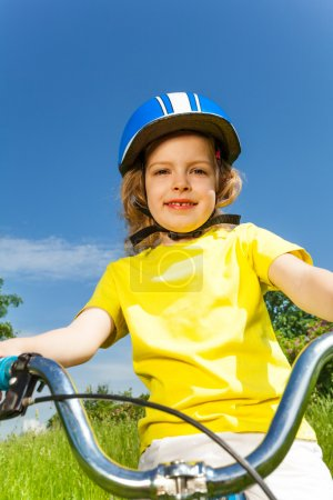 Photo pour Portrait en gros plan d'une jolie petite fille portant un casque bleu sur un vélo - image libre de droit