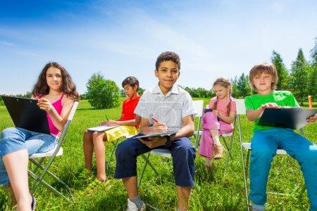 Photo pour Heureux amis dessin sur presse-papiers et assis sur des chaises blanches ensemble à l'extérieur - image libre de droit