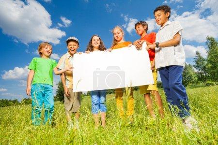 Photo pour Enfants tenant ensemble du papier rectangulaire à l'extérieur - image libre de droit