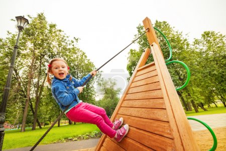 Funny girl climbs by rope