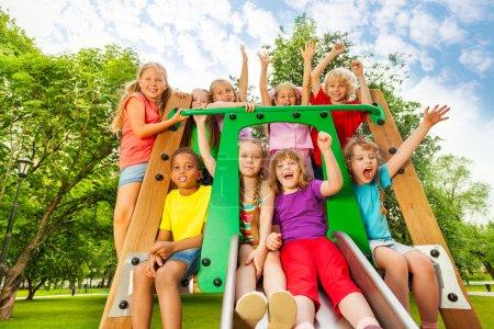 Photo pour Enfants excités du groupe, amis à la recherche de diversité, sur le terrain de jeu parachute avec les bras levés et riant, criant de bonheur - image libre de droit