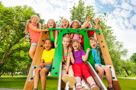 Photo pour Beaucoup d'enfants heureux, drôles et diversifiés sur le parachute de l'aire de jeux avec les bras levés et riant, criant de bonheur - image libre de droit