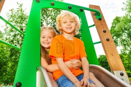 Photo pour Garçon et fille derrière câlin sur chute avec sourire sur aire de jeux en été - image libre de droit