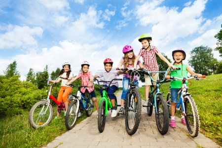 Happy kids in colorful bike helmets