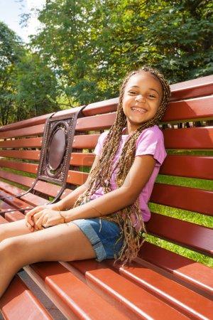 Petite fille noire assise sur un banc