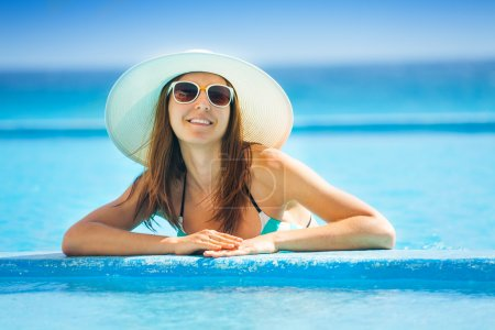 Woman in sunglasses with white hat