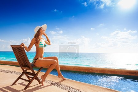Tanned woman on wooden chair