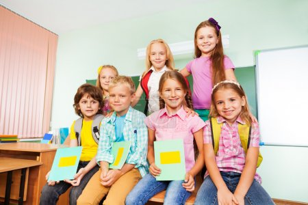 Photo for Smiling schoolchildren sitting together with textbooks near the desk  in school - Royalty Free Image