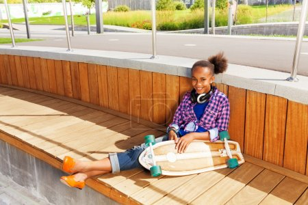 Girl with skateboard on wooden construction