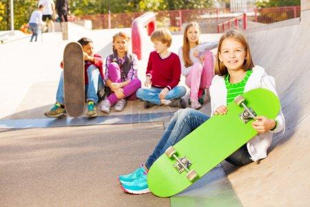 Photo pour Fille avec skateboard et amis assis sur le sol au parc pour enfants pour skateboarders - image libre de droit