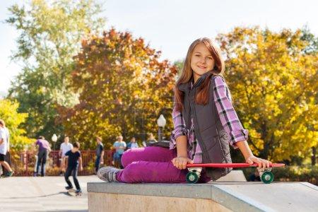 Smiling girl with skateboard