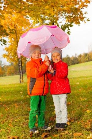 Boy with girl holding umbrella