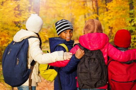 Photo for Back view of kids group standing close with arms on shoulders wearing rucksacks in the autumn forest during daytime - Royalty Free Image