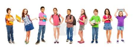 Foto de Grupo de niños de la escuela con buceadores se ven de pie aislados en blanco con libros y mochilas escolares - Imagen libre de derechos