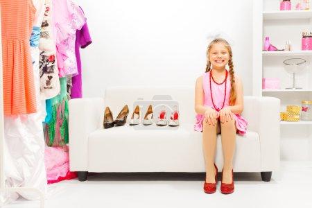 Photo pour Belle petite fille avec des tresses assis sur le canapé en choisissant des chaussures à talons hauts en rangée dans la boutique - image libre de droit