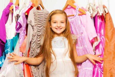 Photo pour Fille de sourire restant parmi des robes et des vêtements lumineux colorés sur des cintres pendant des achats - image libre de droit