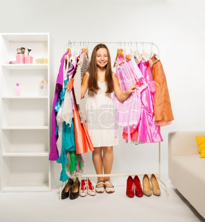 Photo for Smiling girl during shopping between hangers with colorful bright dresses, clothes and women shoes on the floor - Royalty Free Image