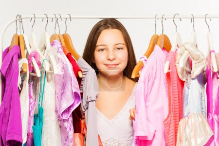 Foto de Girl close-up view standing between hangers with colorful bright dresses and clothes during shopping - Imagen libre de derechos