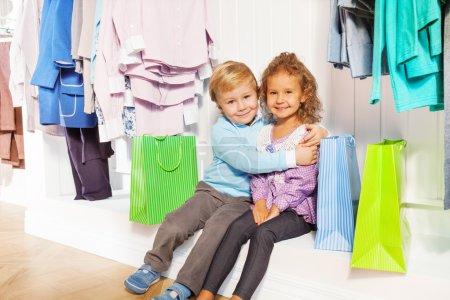 Boy and girl hugging under hangers in shop