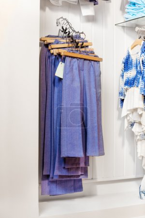 Blue trousers and jeans hanging in shop