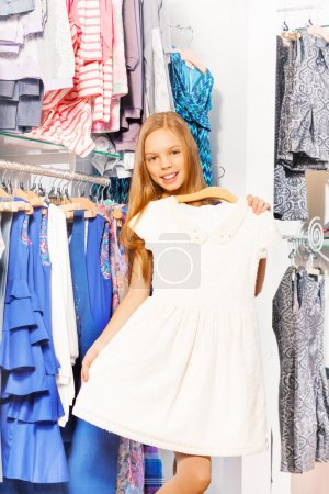 Photo pour Souriant fille tenant et essayant robe blanche sur cintre tout en faisant du shopping dans le magasin de femmes à l'intérieur - image libre de droit