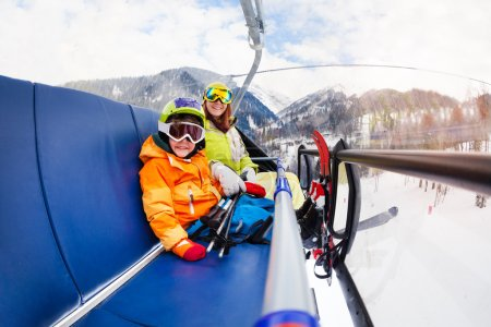 Boy and mother on ski lift chair