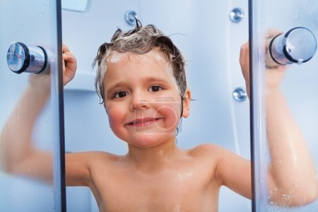 Boy showering with shampoo on hair