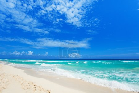 Footsteps on white sand and beautiful waves