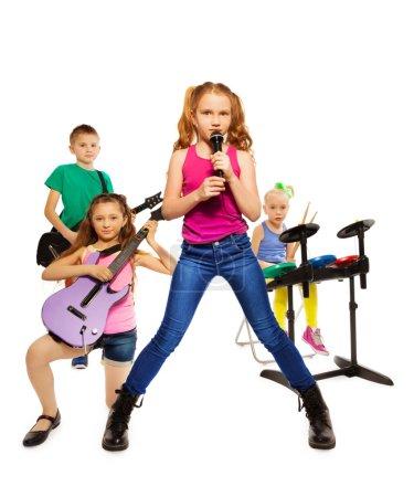 Photo pour Quatre enfants qui jouent sur des instruments de musique ensemble comme groupe de rock et de la fille qui chante comme chanteur en face sur fond blanc - image libre de droit