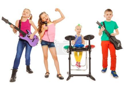 Photo pour Quatre enfants jouer ensemble comme groupe de rock et de la fille qui chante comme chanteur en face sur fond blanc - image libre de droit