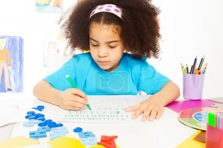 African girl writing letters with pencil