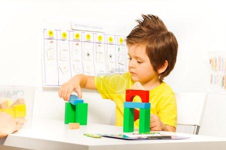 Photo pour Garçon mettre des cubes colorés dans le jeu de construction assis à la table seul à l'intérieur - image libre de droit