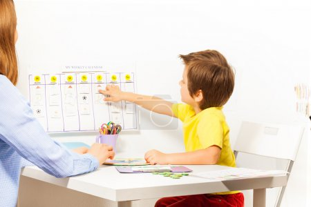 Boy points at activities on calendar