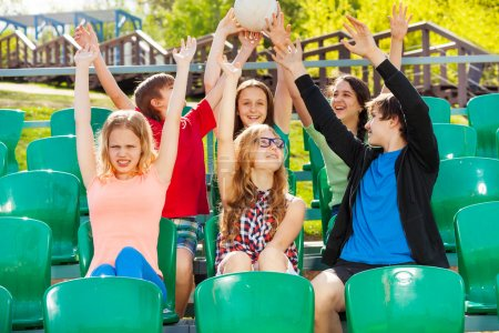 Photo pour Heureux adolescents maintiennent ball et Bravo pour l'équipe pendant le match au stade assis sur la tribune à l'extérieur en été - image libre de droit