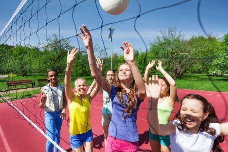 Sportive teenagers playing volleyball together