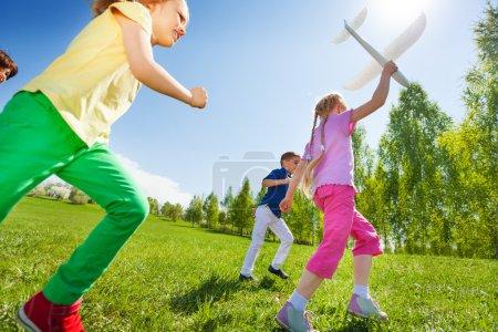 Photo pour Vue d'en bas des enfants qui courent tenant un gros jouet d'avion blanc sur le terrain pendant la journée ensoleillée d'été - image libre de droit