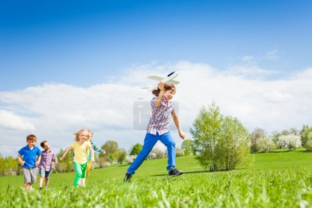 Boy with kids runs with airplane toy