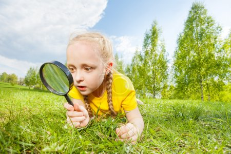 Small girl with magnifier looking
