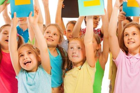 Photo pour Des écoliers soulevant des cahiers d'exercices en l'air et criant - image libre de droit