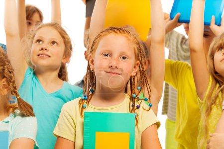 Photo pour Une belle fille heureuse avec le manuel souriant et debout dans la foule grand groupe d'enfants avec les mains levées - image libre de droit