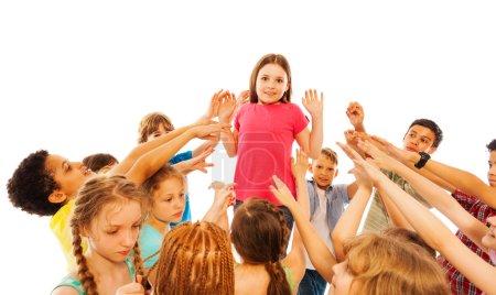 Photo pour Fille est submergée par la popularité en classe debout dans le cercle des enfants pointant du doigt vers elle - image libre de droit