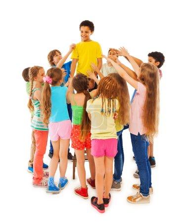 Photo pour Portrait de groupe de toute la longueur des garçons et des filles cercle garçon noir et tendre la main vers lui - image libre de droit